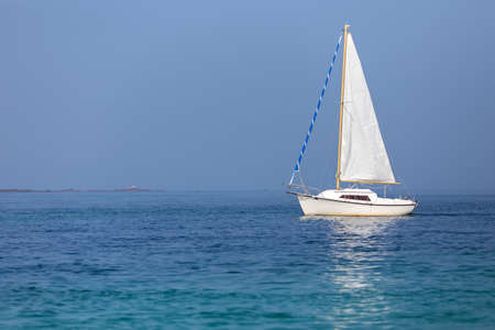 Sailboat on calm sea under a sunny summer day