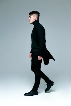 Full length of handsome stylish man in coat