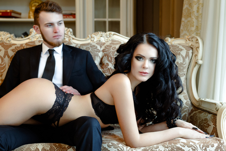 Photo pour Fashion photo romance of sexy lovers couple. woman with black curly hair in black underwear and man wearing suit - image libre de droit