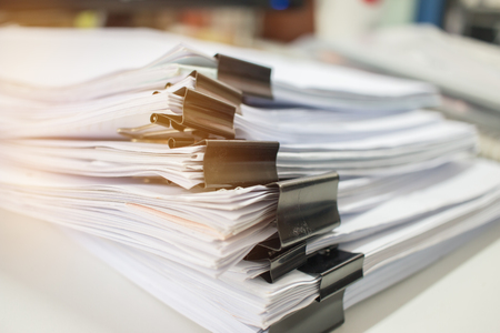 Foto de Paper stack, Pile of unfinished documents on office desk related to business functions. Stack of business papers for Annual Report files, Document is written,drawn,presented. Business offices concept. - Imagen libre de derechos
