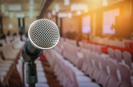 Microphones on abstract blurred of speech in seminar room or front speaking conference hall light, white chairs for people in event meeting convention hall in hotel.