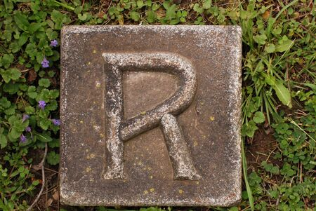 Block with letter R stone, in ground