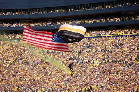 ANN ARBOR, MI - OCTOBER 09: 101st Airborne Division Parachute Demonstration Team member parachutes past the crowd at Michigan Stadium before the Michigan vs. Michigan State football game October 9, 2010.