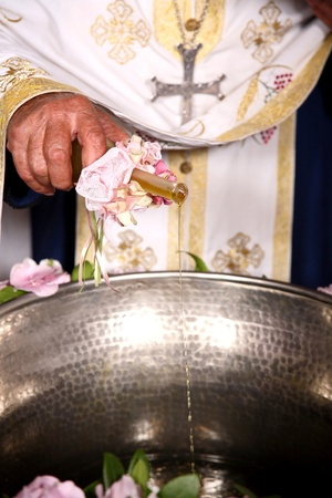 priest add oil on a bowl at an orthodox christening