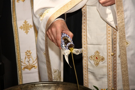 priest add oil on a christening bowl as a part of the orthodox ceremony