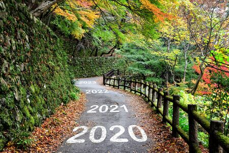 Photo pour Number of 2020 to 2023 on asphalt road surface with maple trees, happy new year concept - image libre de droit