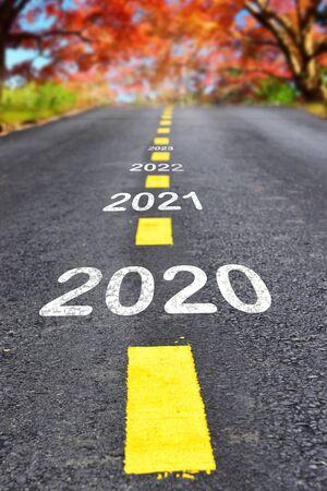 Foto de 2020 to 2023 on asphalt road surface with autumn season background, happy new year concept - Imagen libre de derechos