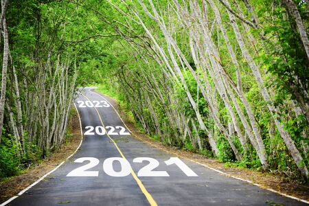 Photo for Tree tunnel with 2021 to 2023 on asphalt road surface, happy new year concept and natural idea - Royalty Free Image