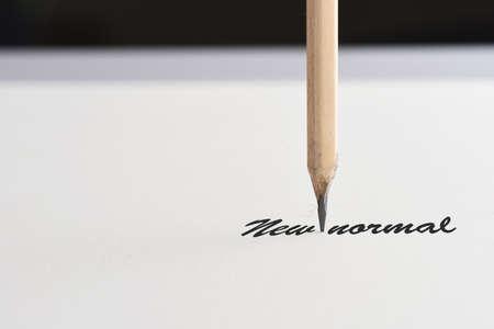 Foto de New normal word with pencil on white paper, business challenge concept and coronavirus Covid-19 idea - Imagen libre de derechos