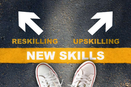 Photo pour New skills development concept and changing skill demand idea. New skills written on yellow line with reskilling and upskilling with white arrow on asphalt road - image libre de droit