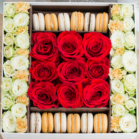 Box with flowers and macaroons close-up top view