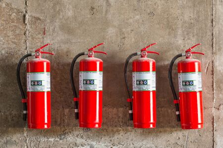 Old fire extinguishers attached on the grunge concrete wall