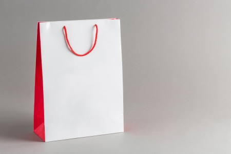 White and red color paper shopping bag isolated on gray background