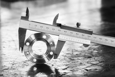 Photo pour Close up vernier caliper measure diameter of stainless steel flange - image libre de droit
