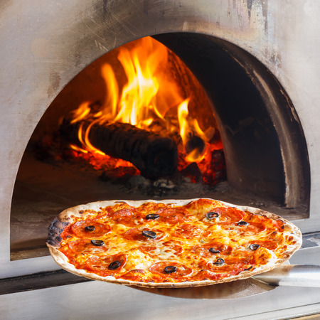 Photo pour Close up pizza in firewood oven with flame behind - image libre de droit