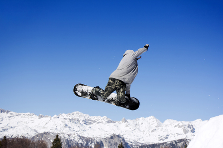Photo pour Extreme Jumping Snowboarder at jump above mountains at sunny day - image libre de droit