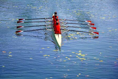 Photo pour Men's quadruple rowing team on blue water, top view - image libre de droit