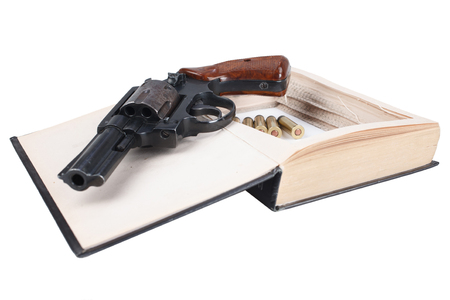 Revolver gun with cartridges hidden in a book isolated on white background