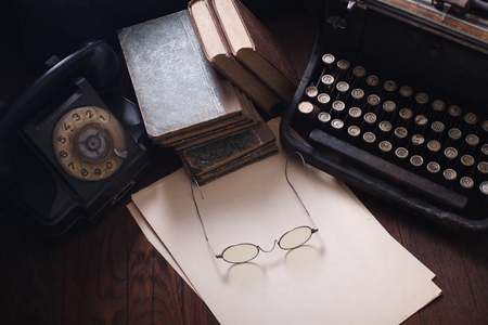 Photo for Old retro phone with vintage typewriter and a blank sheet of paper on wooden table - Royalty Free Image