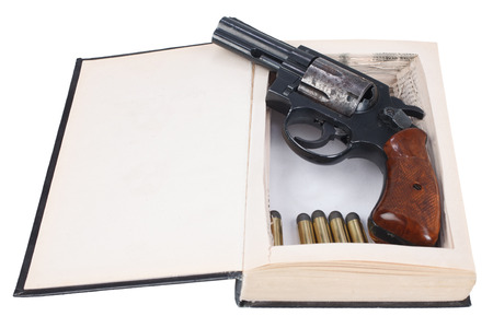 .38 caliber revolver gun with cartridges hidden in a book isolated on white background