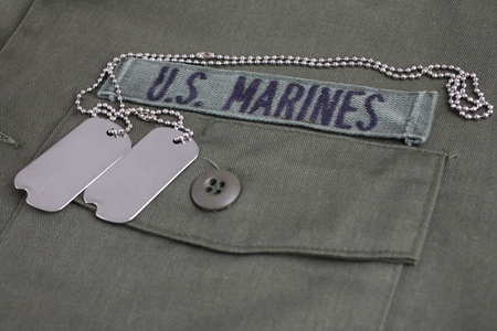 Photo for U.S. MARINES Tape with dog tags on olive green uniform background - Royalty Free Image