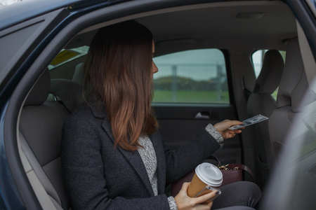 Business woman with mobile phone and coffee in hand paying with driver and ready to leave car