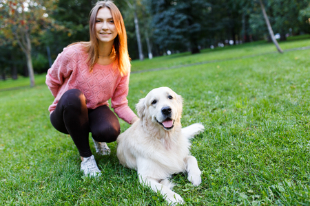 Image of brunette with labrador lying on lawn in summer park