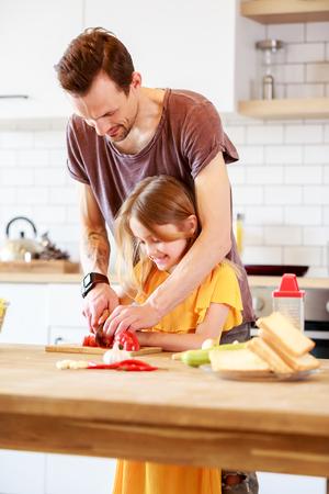 Photo pour Portrait of man with daughter cooking vegetables - image libre de droit
