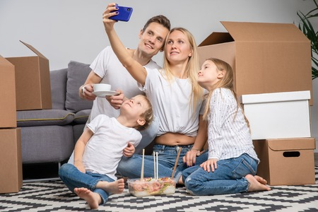 Photo pour Image of man, children and women taking selfie sitting on floor among cardboard boxes - image libre de droit