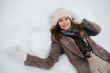 Foto de Photo of blonde in hat lying in snow on walk - Imagen libre de derechos