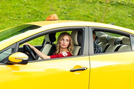 Photo of blonde female driver sitting in yellow taxi on summer