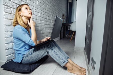 Photo pour Beautiful business lady in casual is using a laptop and smiling while sitting on the floor at home and working - image libre de droit