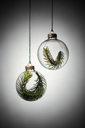 Photo pour Transparent christmas bauble with branch of evergreen tree inside. Creative christmas concept.  - image libre de droit