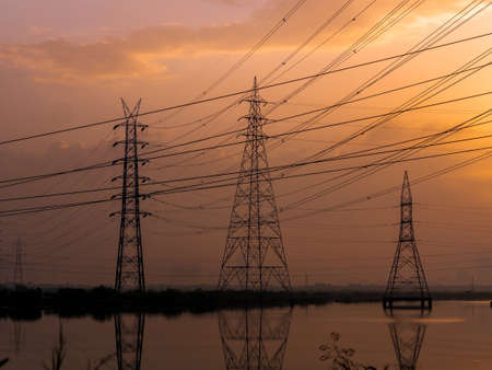 Photo for High-voltage power lines at Sunrise/sunset. electricity distribution station.Saltpans in Mumbai. - Royalty Free Image