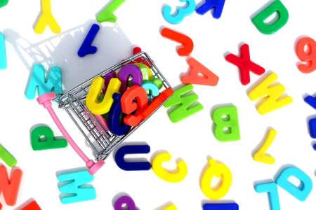 Photo pour Multicolored plastic letters on a white background lie in a mini shopping cart - image libre de droit