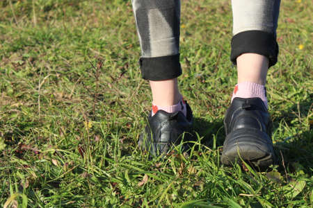 Photo for The legs of a girl walking on the grass are visible - Royalty Free Image