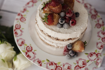 Naked cake with caramelized fruits - strawberries, blueberries, raspberries. Sponge cream cake in floral high plateau, tray. White roses, rustic background