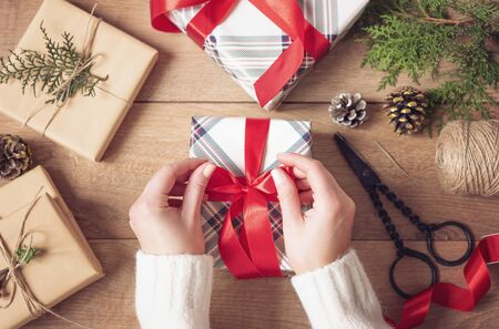 Photo for Christmas Background. Female Hands Tying A Red Bow. Woman Packing Christmas Gifts. Holiday Concept. Top View, Flat Lay, Advent Gift - Royalty Free Image