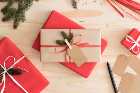 Photo for Red and kraft christmas gifts surrounded with pine cones, leaves and twine on a wooden table. - Royalty Free Image