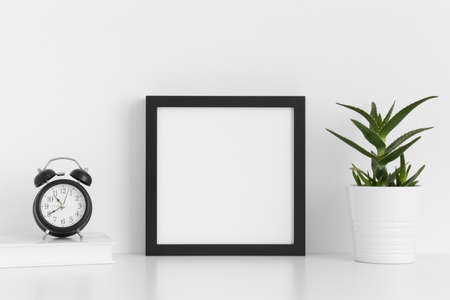 Photo pour Black square frame mockup with a aloe vera in a pot and workspace accessories on a white table. - image libre de droit