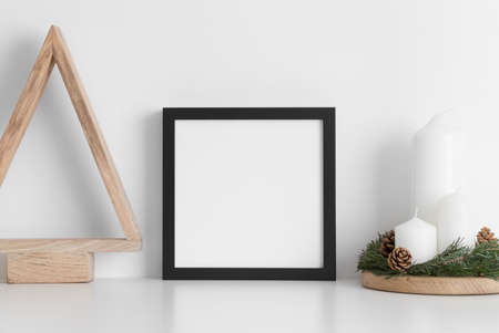 Photo for Black square frame mockup with a wooden tree and candles on a white table. Christmas decoration. - Royalty Free Image