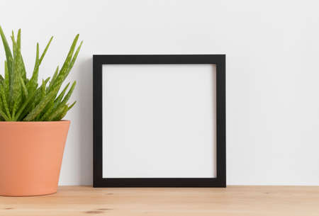 Photo pour Black square frame mockup with a aloe vera in a ceramic pot on a wooden table. - image libre de droit