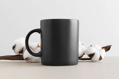 Photo for Black mug mockup with a cotton branch on a beige table. - Royalty Free Image