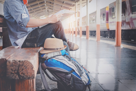 Foto de Side portrait of a  young man traveler sitting with map choose where to travel and bag waiting for train, vintage tone filter effected - Imagen libre de derechos