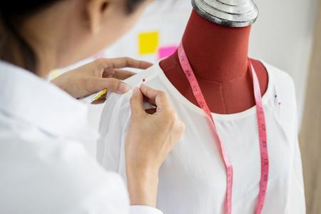 Photo pour Asian tailor adjusts garment design on mannequin in workshop make a little adjustment to her work on model in the studio - image libre de droit