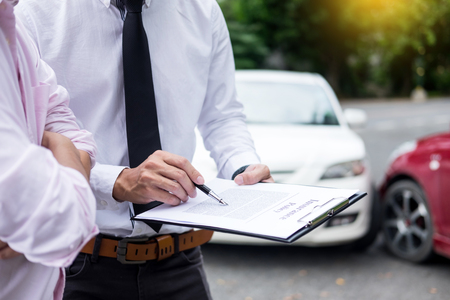Photo pour Insurance agent writing on clipboard while examining car after accident claim being assessed and processed - image libre de droit