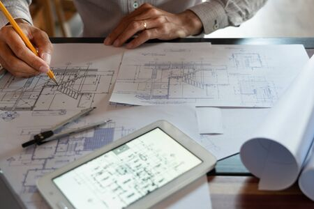 Foto de Confident engineer team working with Blue Print with architect equipment discussing and Planning work flow construction project. with partner at the table in office work site. - Imagen libre de derechos