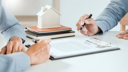 Photo pour broker agent and customer holding pen, the policyholder and explain discussing for concerning mortgage loan offer for and house insurance - image libre de droit