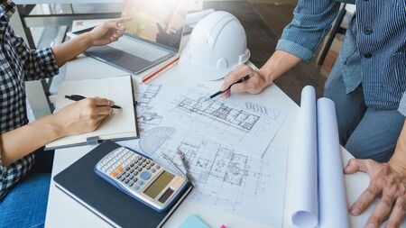 Foto de Cooperation Corporate designers in the office are working on a new project Planning blueprint Design at construction site at desk in office - Imagen libre de derechos