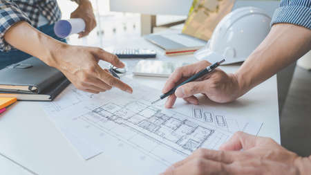 Photo pour engineer Hand Drawing Plan On Blue Print with architect equipment discussing the floor plans over blueprint architectural plans at table in a modern office - image libre de droit
